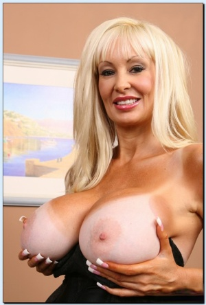 Mature gal Brittany Oneal revealing her huge round boobs and inviting cunt