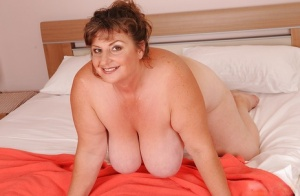 Mature plumper with huge saggy jugs and hairy cooter posing on the bed