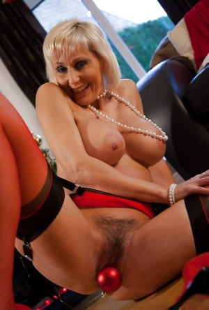 Glamorous mature vixen in nylons teasing her pussy under the Christmas tree