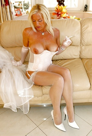 Glamorous mature vixen in snazzy lingerie and nylons smoking a cigarette
